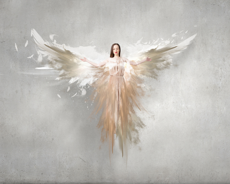 Beautiful woman in long dress with wings on concrete background