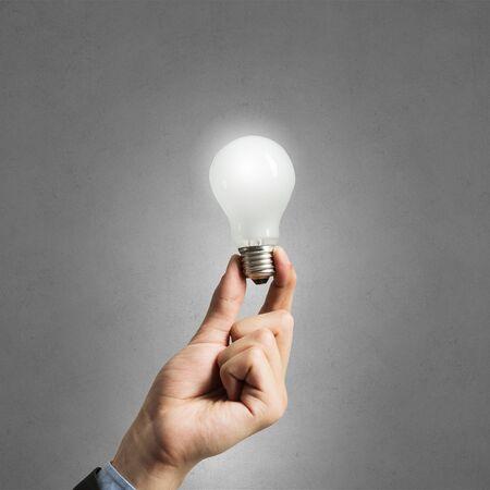 lit: Lit lightbulb held in hand on gray background