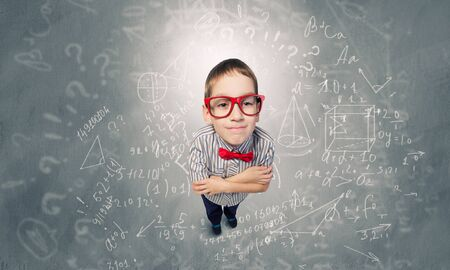 Top view of cute schoolboy in red glasses on chalkboard background Stock fotó