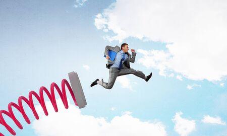 businessman jumping: Businessman jumping on springboard as progress concept