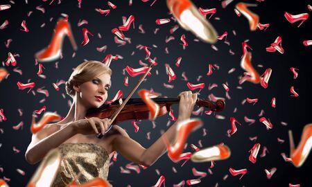 sotto la pioggia: Beautiful young woman playing violin under rain of falling shoes Archivio Fotografico