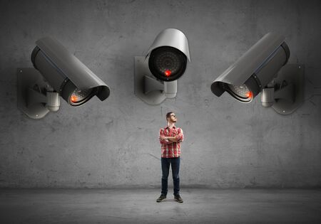 under control: Young man in casual under control of CCTV Stock Photo