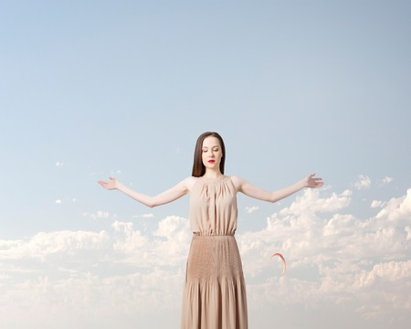 Beautiful woman in long dress with wings in clear sky