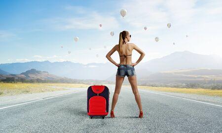 Beautiful woman in swimsuit standing on asphalt road