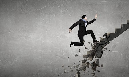 collapsing: Young businessman walking up collapsing staircase representing success concept