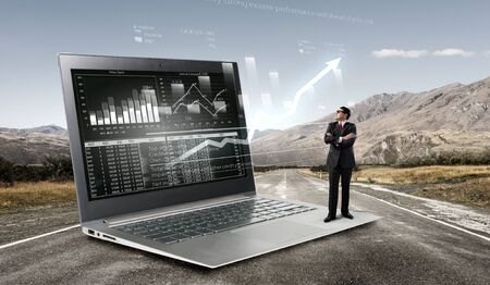 average guy: Adult businessman standing on huge laptop and graphs and diagrams on screen