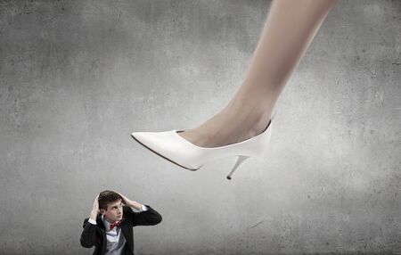 henpecked: Businesswoman foot stepping on tiny businessman presenting power concept