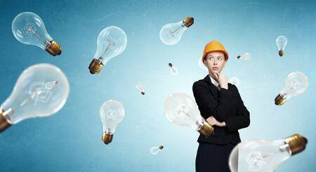woman engineer: Attractive woman engineer in helmet and glass light bulbs Stock Photo