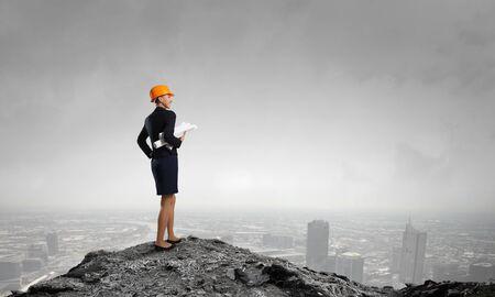 woman engineer: Attractive woman engineer wearing helmet with paper project in hands