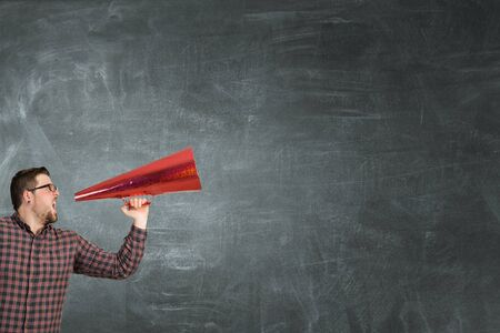 amplify: Hipster man screaming emotionally in red paper trumpet