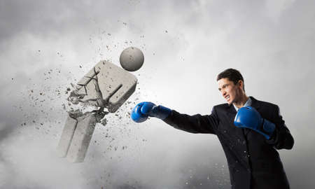 opponent: Handsome determined businessman wearing boxing gloves fighting opponent