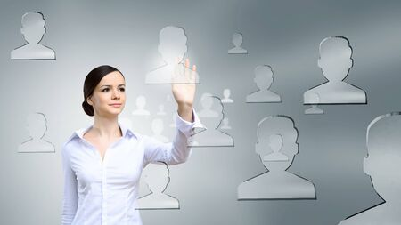 virtual community: Young elegant businesswoman touching glass icon on screen Stock Photo