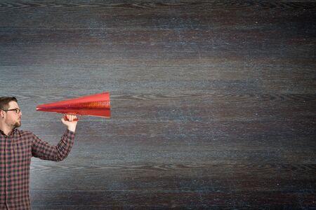 loud hailer: Hipster man screaming emotionally in red paper trumpet