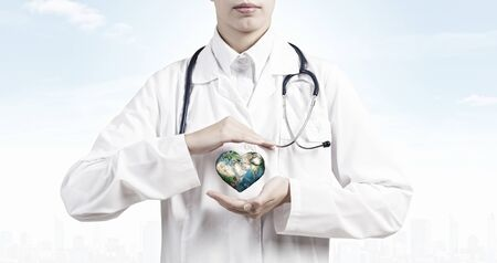 holding close: Close up of female doctor holding Earth planet in hands. Stock Photo
