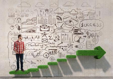 El hombre joven en ocasional contra la pared con bocetos de estrategia empresarial