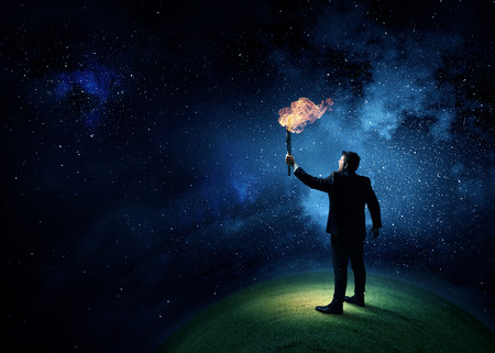 Young businessman in darkness holding burning torch in hand Reklamní fotografie
