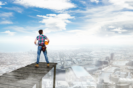 engineering clipboard: Rear view of man engineer standing on wooden platform against city landscape