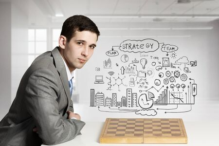 Focused young businessman and chess board on table