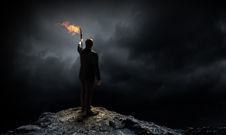 Young businessman in darkness holding burning torch in hand Archivio Fotografico