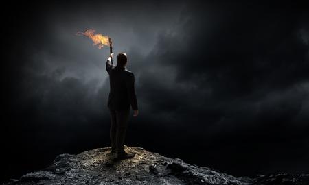Jonge zakenman in het donker met brandende fakkel in de hand