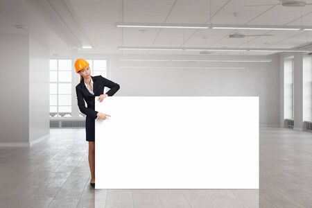 woman engineer: Attractive woman engineer pointing with finger at white blank banner Stock Photo
