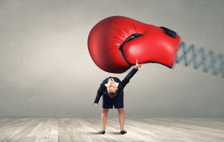 Young determined businesswoman fighting boxing glove on spring Stock Photo
