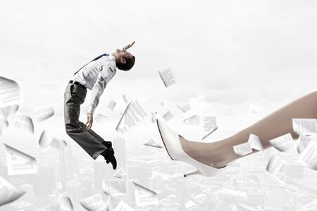 dismiss: Businesswoman foot giving kick to businessman presenting power concept