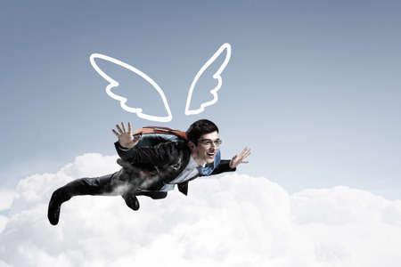 business challenge: Cheerful businessman with parachute on back flying in sky