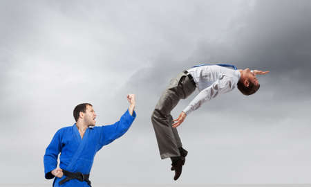 Young determined karate man fighting with businessman in suit Stock Photo