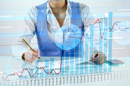 sales report: Hands of businessperson sitting at desk writing average sales report