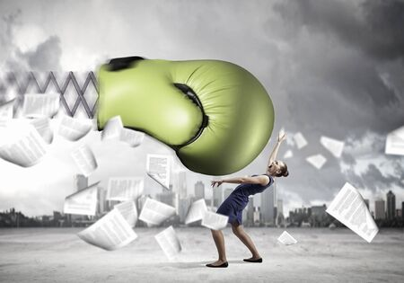 beat the competition: Young determined businesswoman fighting boxing glove on spring Stock Photo