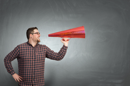 emotionally: Hipster man screaming emotionally in red paper trumpet