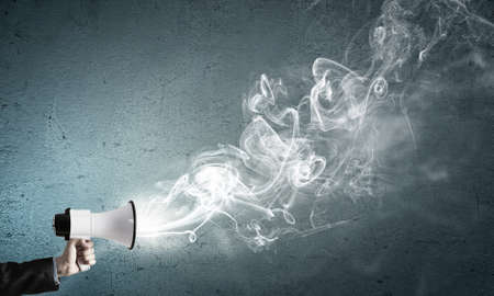 fume: Hand of businessman with megaphone and fume flying out