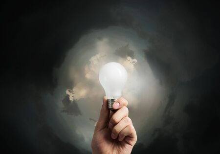 wattage: Lit lightbulb held in hand on dark background Stock Photo