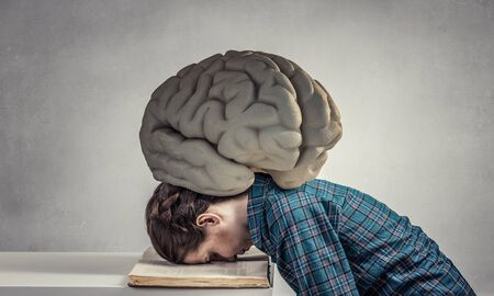 oppressed: Student girl pressed with brain to opened book pages