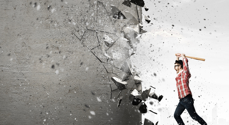 Young man with baseball bat in anger breaking wall Stock Photo