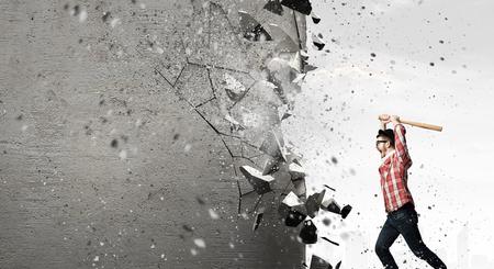 Hombre joven con el bate de béisbol en la pared rompiendo la ira