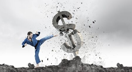 man power: Young determined karate man breaking with leg concrete dollar sign