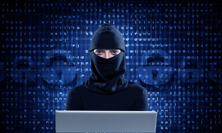 Hacker woman in dark clothes using laptop against digital background