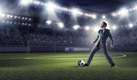 Young businessman in suit playing football at stadium Stok Fotoğraf