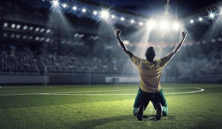 Voetballer vieren de overwinning terwijl win cup Stockfoto