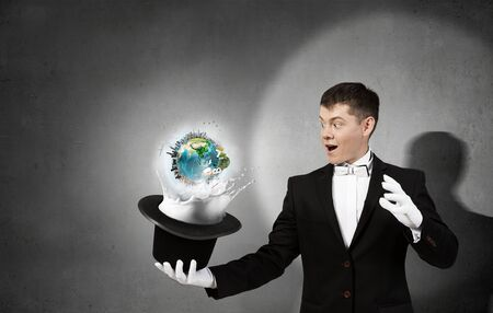 Young cheerful businessman making tricks with magic hat. Elements of this image are furnished by NASA Banco de Imagens
