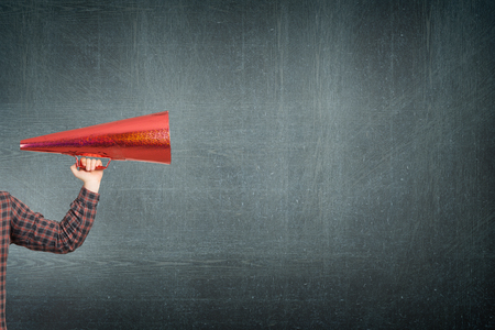 amplify: Hand of man holding red paper trumpet