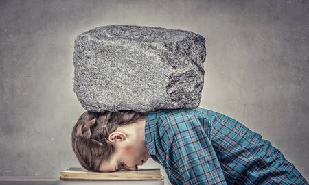 suppressed: Student girl pressed with stone to opened book pages
