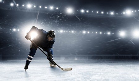 hockey puck: Hockey player in lights at ice rink