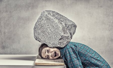 oppressed: Student girl pressed with stone to opened book pages