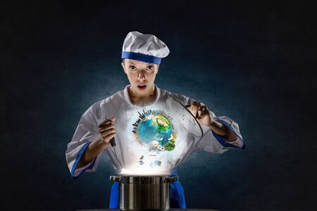 Pretty woman cook in hat and apron with doing magic above pot. Elements of this image are furnished by NASA