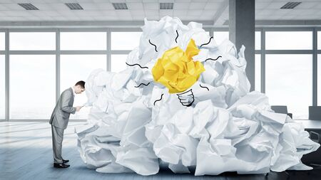 hard to find: Troubled businessman in office and heap of paper balls