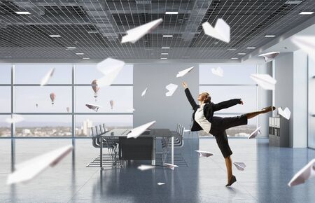 Happy young businesswoman dancing in modern office