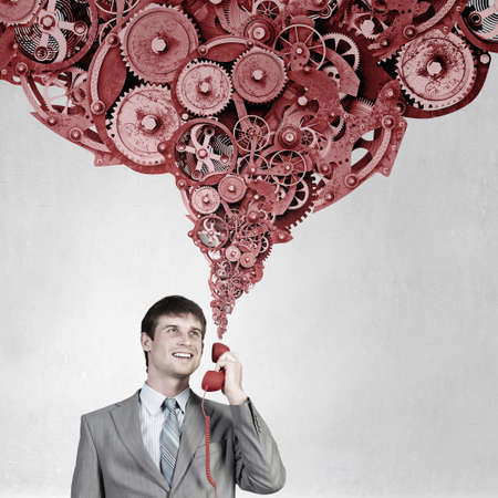 phone handset: Handsome businessman talking on red phone handset Stock Photo